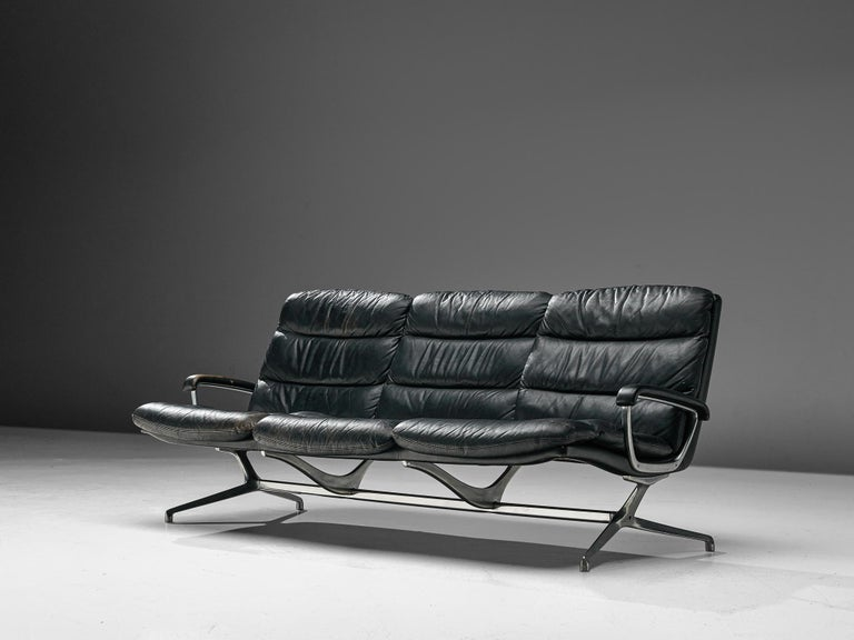 Paul Tuttle, three-seat sofa, for Strässle International, leather and cast aluminium, Switzerland, 1960s.  This sofa designed by Paul Tuttle is upholstered in black leather and has a striking aluminium frame an armrests, giving the sofa a very