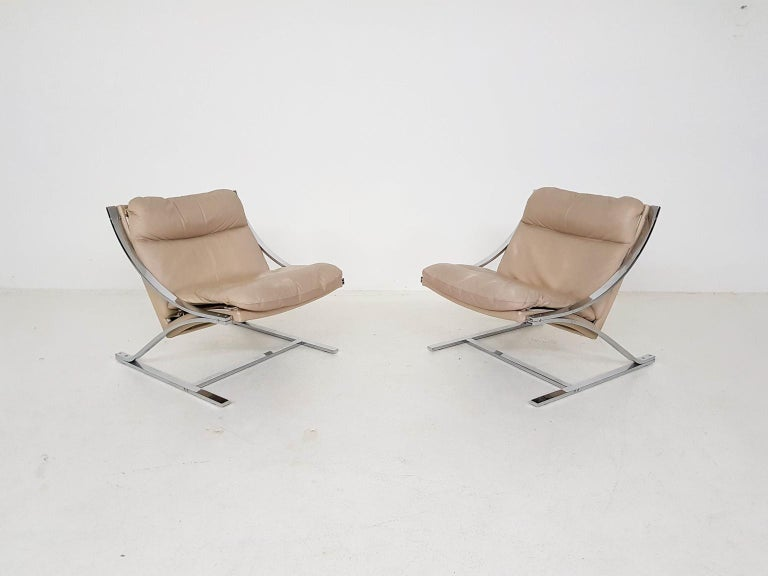 Pair of high quality chromed metal lounge chairs with an off-white leather upholstery. Designed by Paul Tuttle for Strässle, Switzerland in 1968.  Nice pair with Z shaped frame, which explains the name Zeta (the sixth letter in the Greek