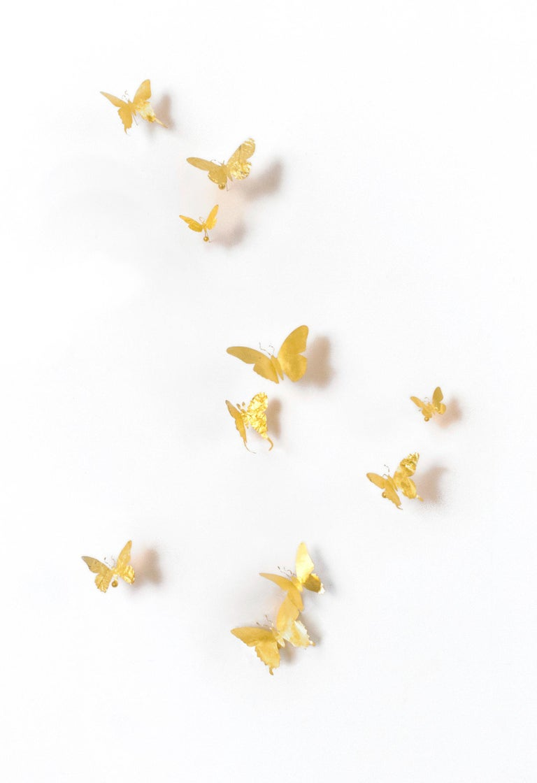 A set of 10 butterflies, made from found aluminum cans, which are cut and then covered with gold leaf. The cans are often found, crushed, on the street. Any wrinkles, tear, or wear in the aluminum is intentional.  The butterflies are modeled after