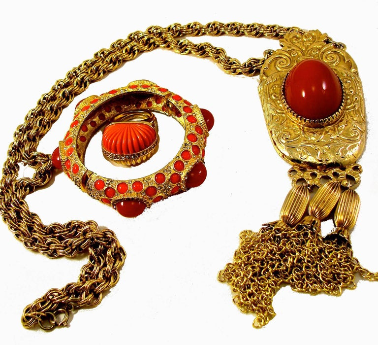This three-piece statement set was designed by Pauline Rader in the 1970s and features a massive 7.5in pendant on a chunky chain necklace, with matching clamper bracelet and cocktail ring.    Made from an ornate gold tone metal setting, the pendant