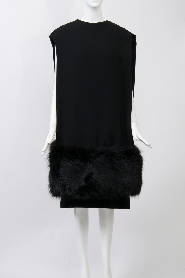 Stunning Pauline Trigère 1970s ensemble in black wool crepe, the simple dress underneath an unusual reverse cape/shawl terminating in deep black fox trim at the hems. The cape can be worn with the opening back or front, but looks most dramatic with