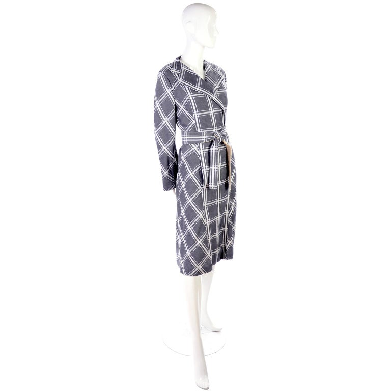 This is a lovely Pauline Trigere vintage coat dress in charcoal gray and white thick cotton plaid.  The long sleeves flair at the ends. The dress is closed at the bottom and the top secures with two hook and eyes. The tie waist belt is lined in