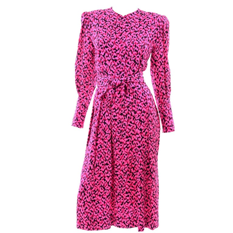 This is a vintage Pauline Trigere pink, red and black abstract print long sleeve silk dress. The dress has puff sleeves with slim zippered cuffs hat have the same pleats found on the rest of the dress  High v-neckline and boxy shoulder pads. The