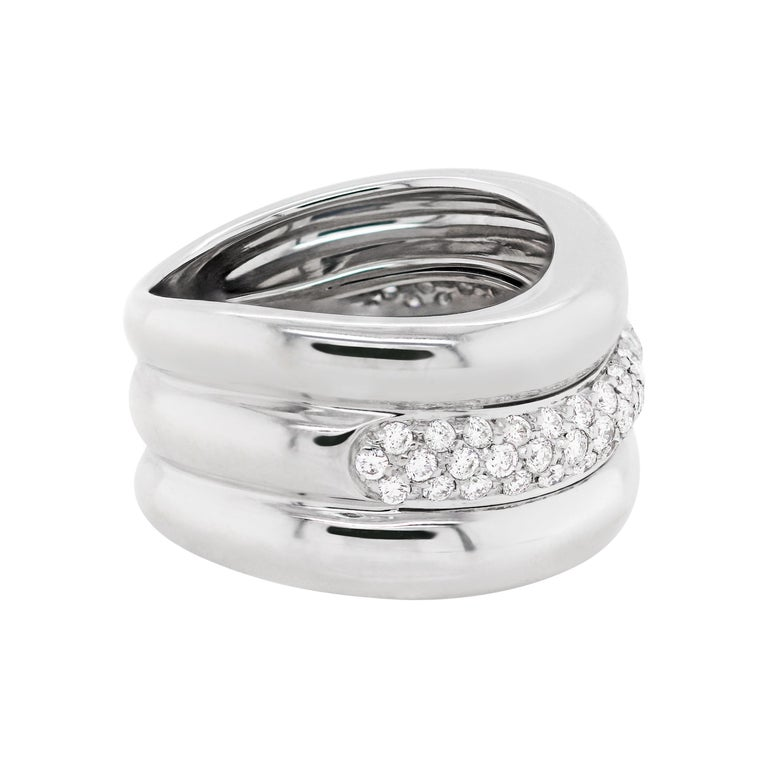 This modern waved design 18 carat white gold mount is beautifully set with a row of 55 pavé set round brilliant cut diamonds totalling to approximately 0.60ct. The band weighs 10.67gr and measures 11.5mm in width. Hallmarked 750. UK finger size 'I