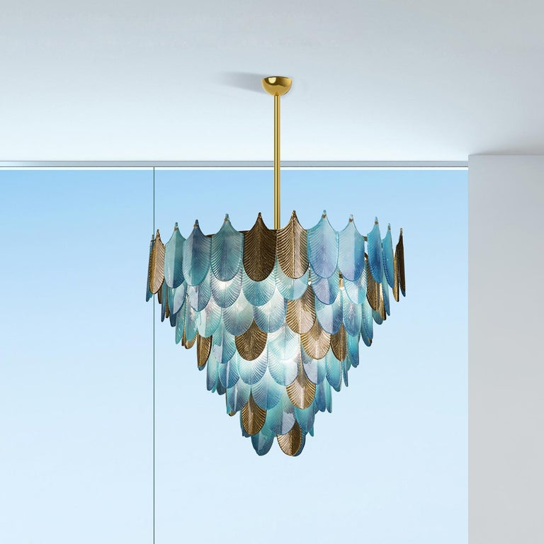 This chandelier is a work of functional art and a superb sculptural accent for a refined home, part of the Home Couture collection. Its structure in brass supports a myriad of elements evoking the silhouette and texture of peacock feathers and made