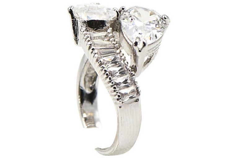 Impressive costume cubic zirconia (CZ) cocktail ring that imitates a pear shaped diamond bypass ring. The pear CZs look like 2.75 carat each diamonds mounted with baguettes in rodium plated sterling silver hardware. Marked 925 for sterling silver.