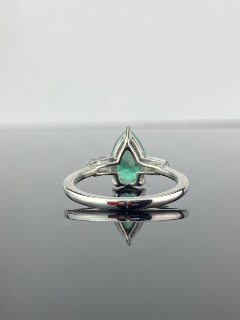 A beautiful, versatile, 0.83 carat natural Colombian Emerald and 0.2 carat Diamond baguette three-stone engagement ring, set in Platinum. Currently sized at US 6, can be resized.