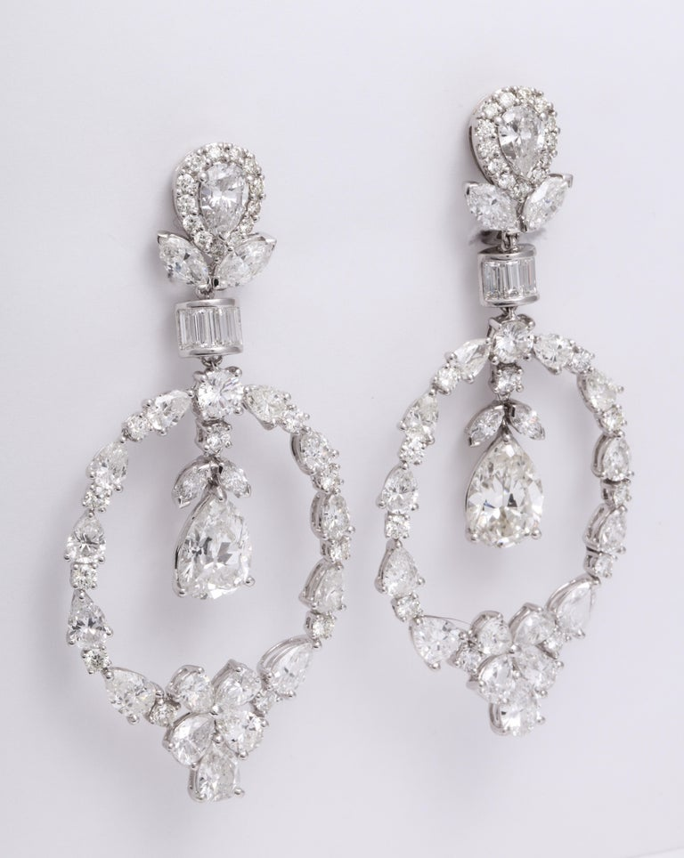Elegant and showstopping handmade 18 Karat white gold chandelier earrings mounted with inverted pear shape diamond studs within a round brilliant-cut, marquise, and baguette diamond frame, suspending an articulating pear shape and round