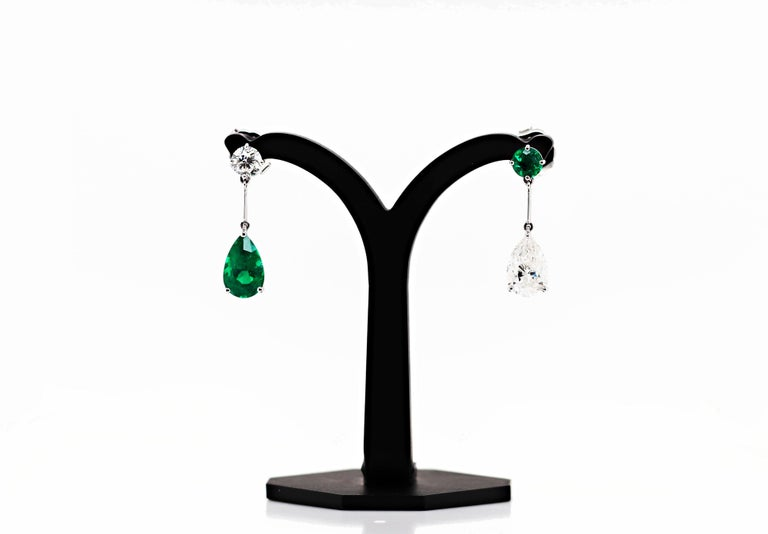 Magnificent unique pair of handmade drop earrings, each featuring an emerald and diamond. The first is set with a vibrant green pear shape emerald weighing 2.97ct in a three claw open back setting, hanging off a round brilliant cut diamond in a four