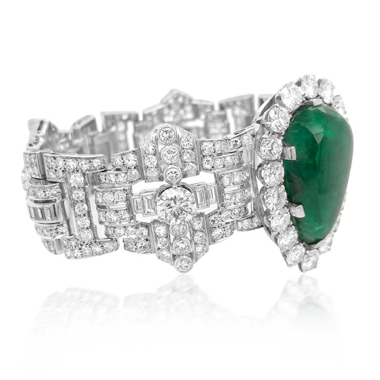 This opulent, quintessentially Retro design bracelet is rendered in solid 18K, weighing 84.77 grams and measuring approx. 19.2 cm (7.55 inches) long and 38mm (1.5 inches) wide. The impressive bracelet is centered with a pear shape cabochon emerald,