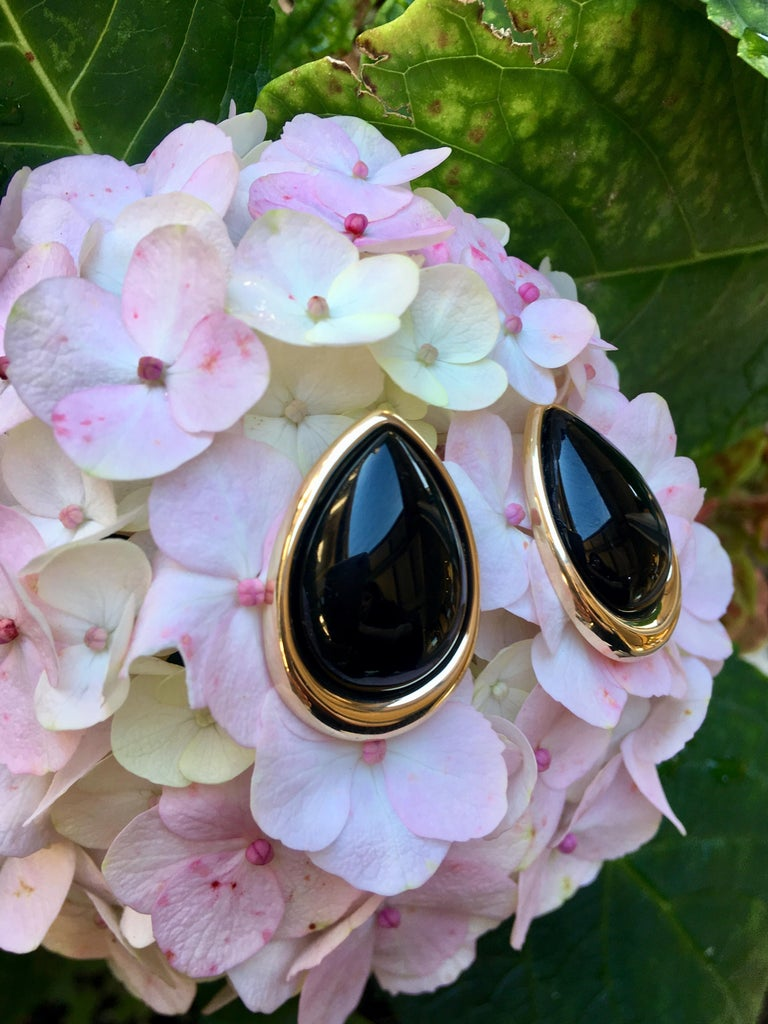 Modernistic, elegant, large, pear shaped, rounded black onyx stones are bezel set in highly polished 14 karat yellow gold, with posts and friction backs for pierced ears.  Well designed and well made, these earring feature posts which are nicely