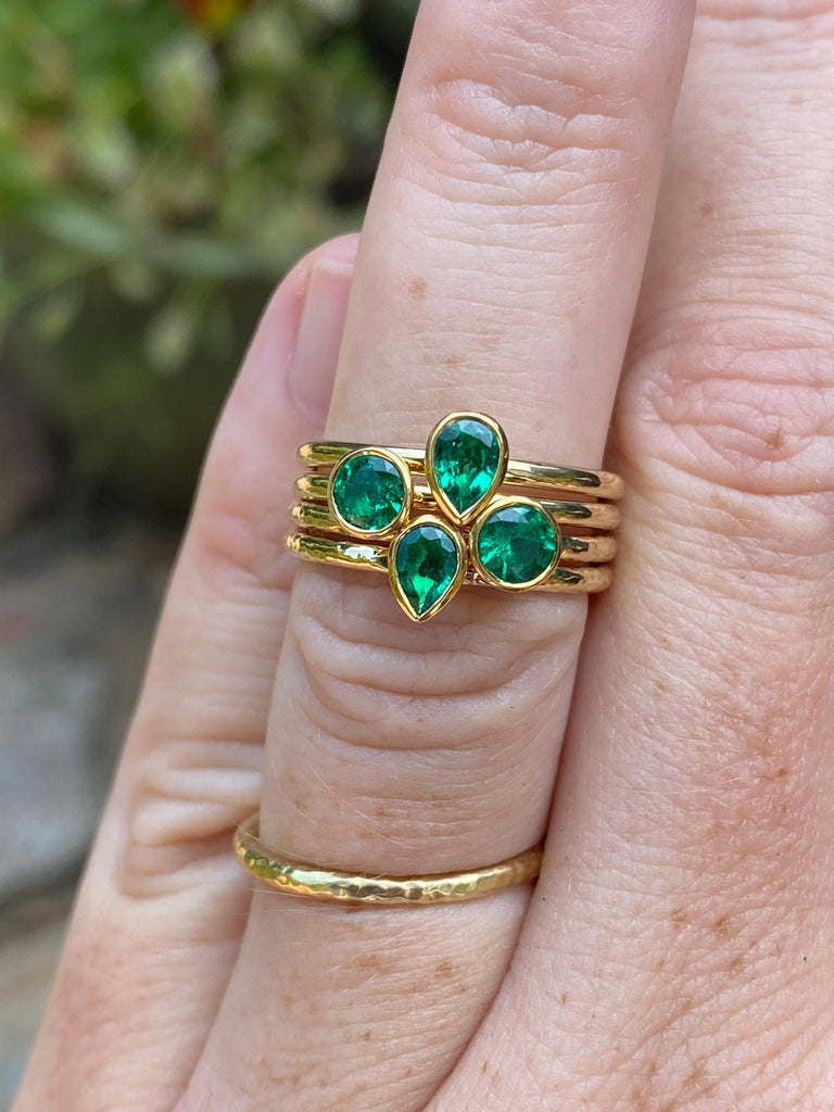 A clean and bright Colombian pear shaped emerald is featured in this hand forged stacking ring. It is crafted in 22 and 18 karat gold by our master goldsmith in California. The price as listed is for one ring.   -Colombian emerald pear of 0.35
