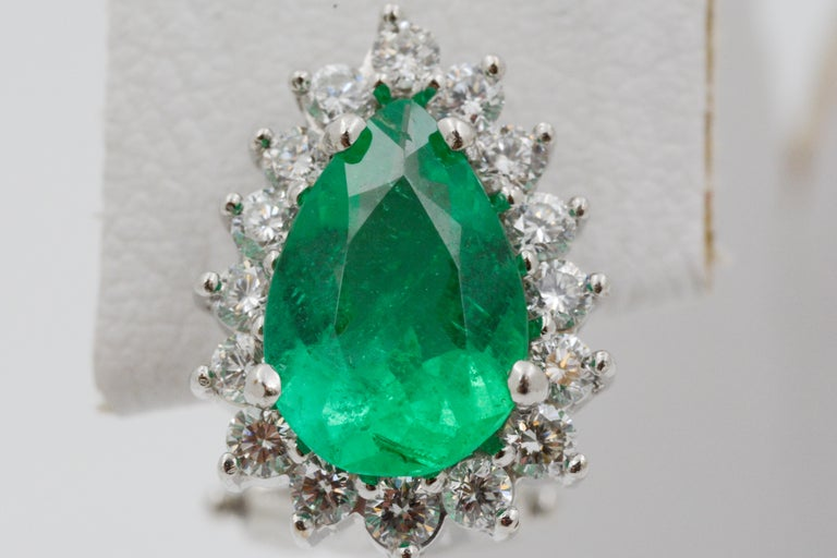These vibrant 18k white gold earrings feature two pear shaped emeralds, weighing a total of 2.72 carats. 32 round diamonds, weighing a total of .32 carats with G coloring and VS clarity, surround the emeralds. The earrings have omega post backs.