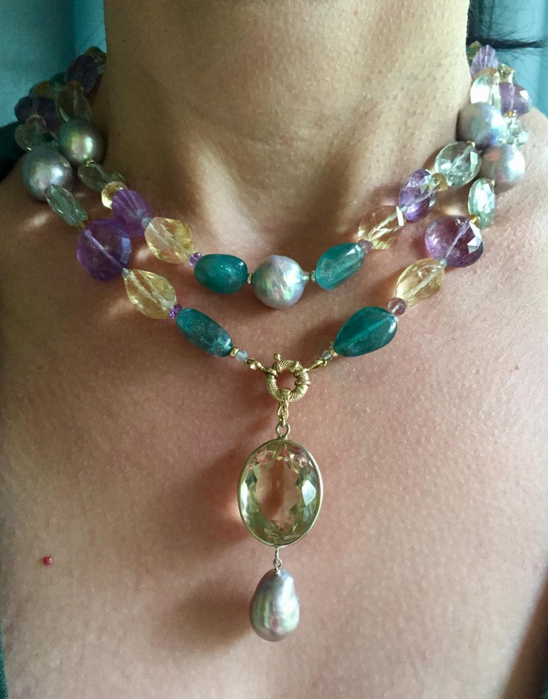 This pearl, amethyst, citrine, and blue topaz necklace with 14k white and yellow gold is beautifully colorful, with different semi-precious stone beads. The large baroque grey pearls, green and purple amethyst, citrine, and London blue topaz shine