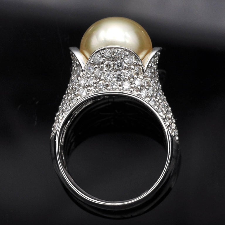 A golden pearl nested in a flower like 18 Karat gold cocktail ring pavé set with white diamond . The design is timeless and fashionable.  White diamonds: 2.35 carat 18KT gold , French Hallmark stamp Pearl: 12mm