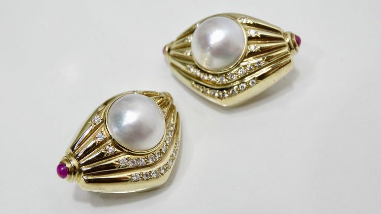 Complete your look with these stunning earrings! Circa 1970s, these ribbed geometric shaped earrings are 14k Gold and set with a large natural Pearl. Features Cabochon cut Pink Sapphires are on both ends, five rows of round brilliant cut Pave set