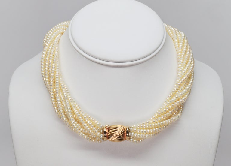 This elegant two piece necklace and bracelet set is abundantly strung with ten strands of 3.75 freshwater button pearls. The necklace, in a sixteen inch length, features a substantial fourteen carat yellow gold decorative bow tie clasp that can be