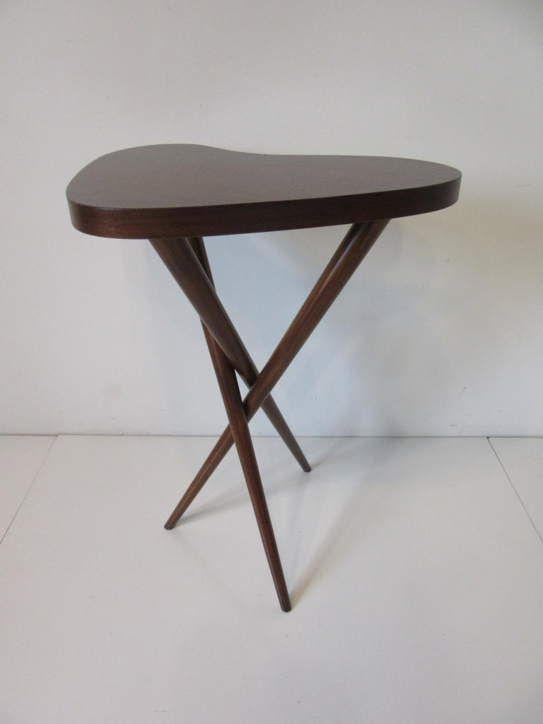 A pedestal table with crossed leg base and biomorfic walnut top in the manner of Widdicomb and T.H. Robsjohn Gibbings. A well crafted and designed pedestal for your sculpture or fine art piece.