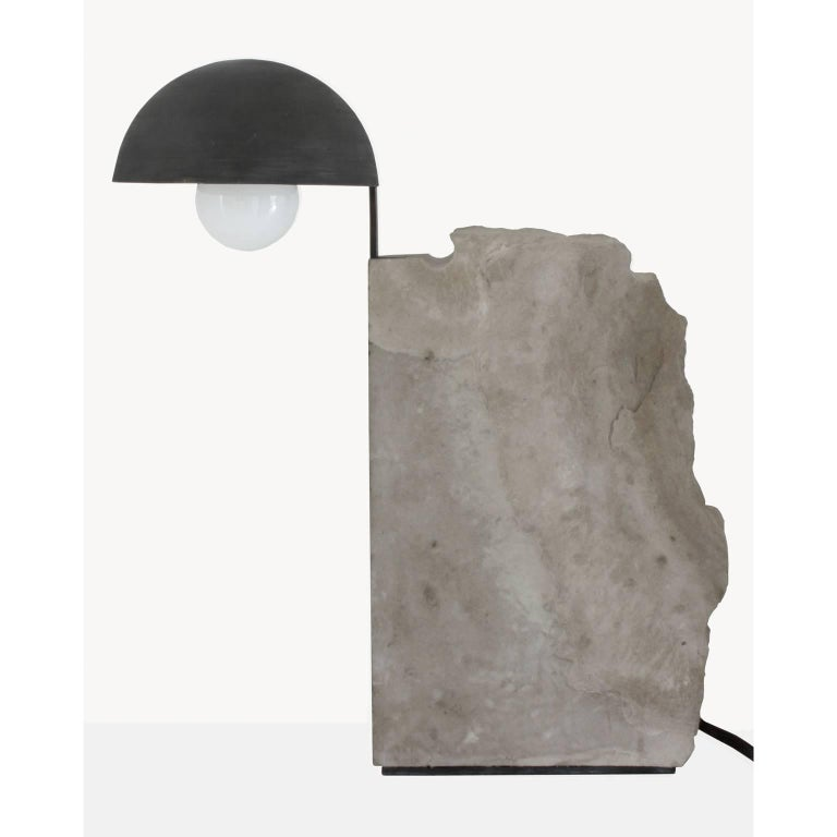 Brazilian contemporary table lamp by designer Gustavo Neves Aeon collection The Pedra table lamp Materials: stone (limestone), metal (brass) darkened with manual treatment. Brazil 2017 For this project, Gustavo Neves designed the collection Æon