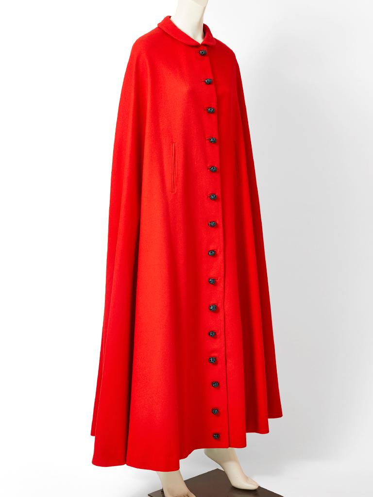 Pedro Rodriquez, red wool, maxi cape, having a small round collar , slits for the arms and black sculpted button closures going down the middle front of the cape.