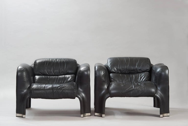 """Pair of """"Pohjola"""" lounge chairs in black plastic, upholstered in black leather. They need to replace only the filling, the leather is very good condition, this restoration work can be done by us."""