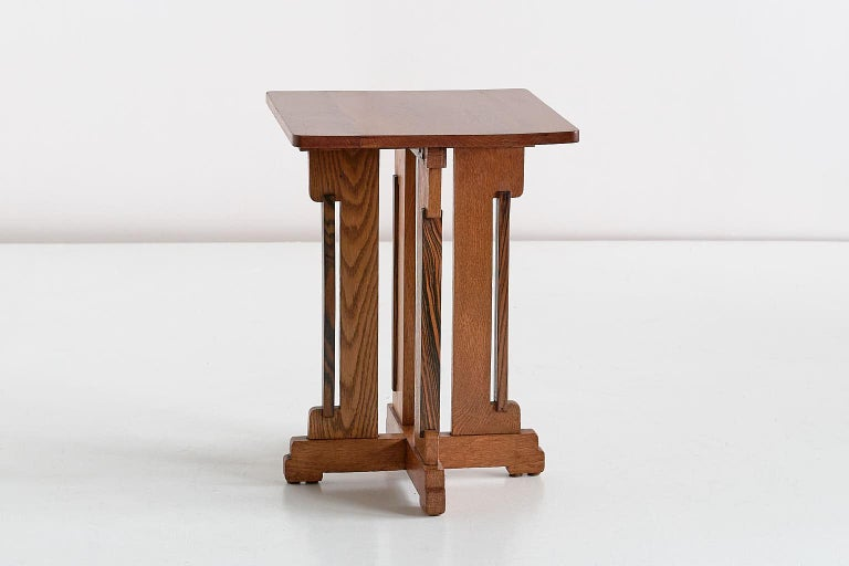 This rare side table was designed by P.E.L. Izeren and produced by the Dutch company Genneper Molen in 1930. The frame and top are made of solid oak, with four contrasting side slats in Macassar Ebony wood. The geometric, tiered base and the