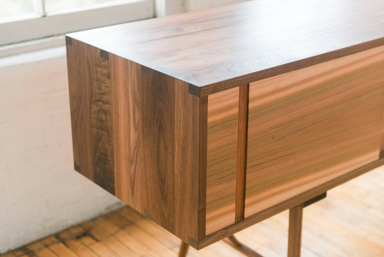 Phloem Studio Pelican cabinet solid walnut wood credenza with sliding doors. The hardwood case has hand crafted exposed trunk finger joinery up on a base with tall turned tapered and braced legs. Three sliding doors travel on waxed hardwood tracks