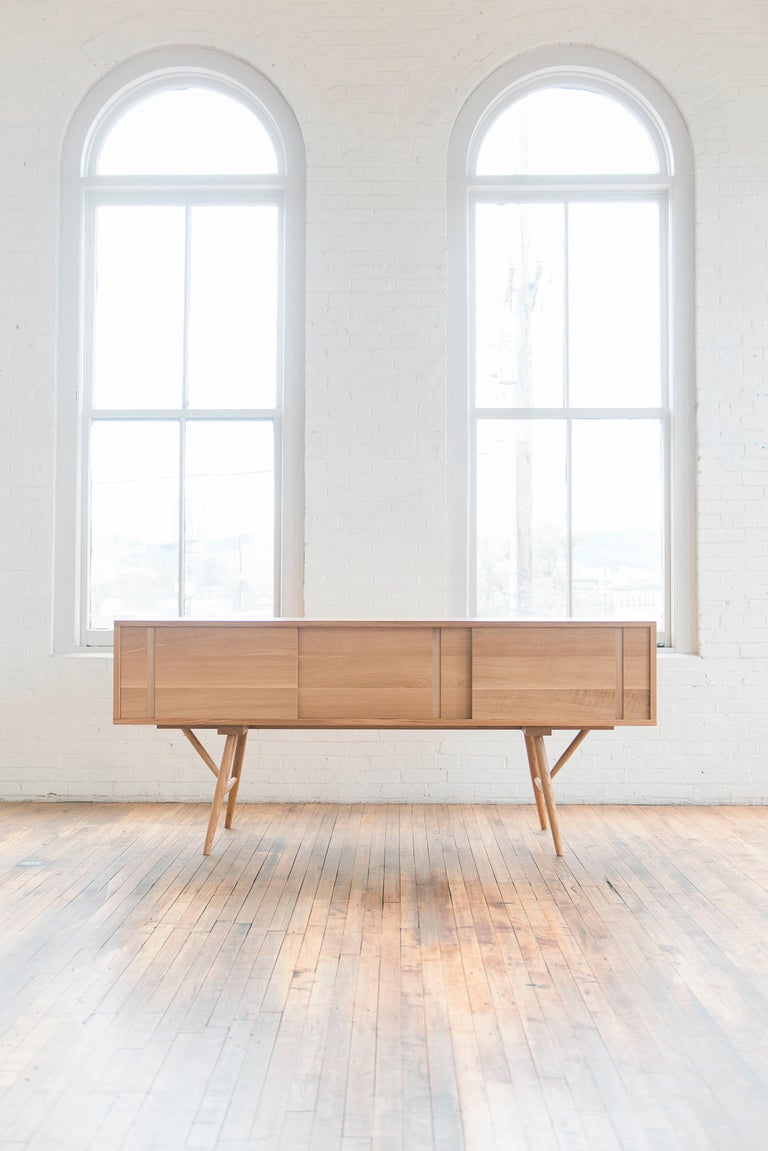 Phloem Studio Pelican cabinet solid white oak wood credenza with sliding doors. The hardwood case has handcrafted exposed trunk finger joinery up on a base with tall turned tapered and braced legs. Three sliding doors travel on waxed hardwood tracks