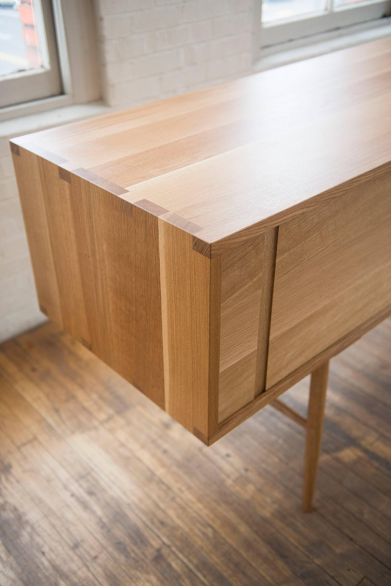 Contemporary Pelican Cabinet, Modern White Oak Sideboard with Sliding Doors and Turned Legs For Sale