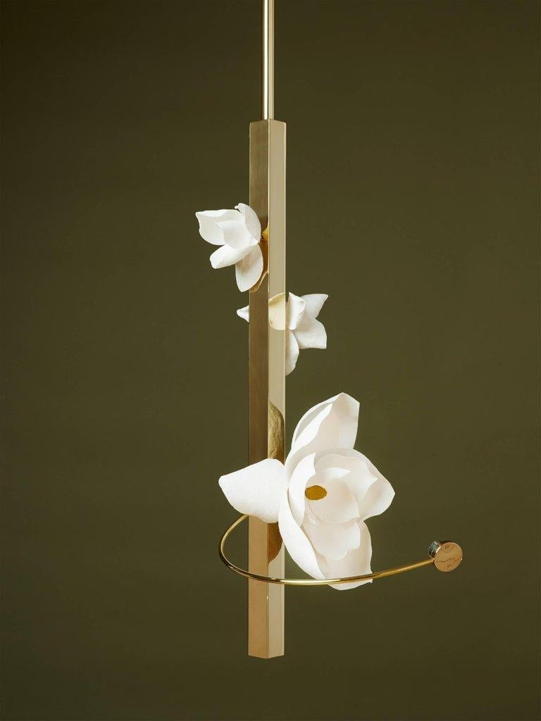 Lure transforms a flower's transient beauty into a lasting light. In this fixture, a cast cotton paper flower is spotlit by a suspended LED light source. Held by a slender brass arc, the light shines brightly on a blossom built of hand-sculpted