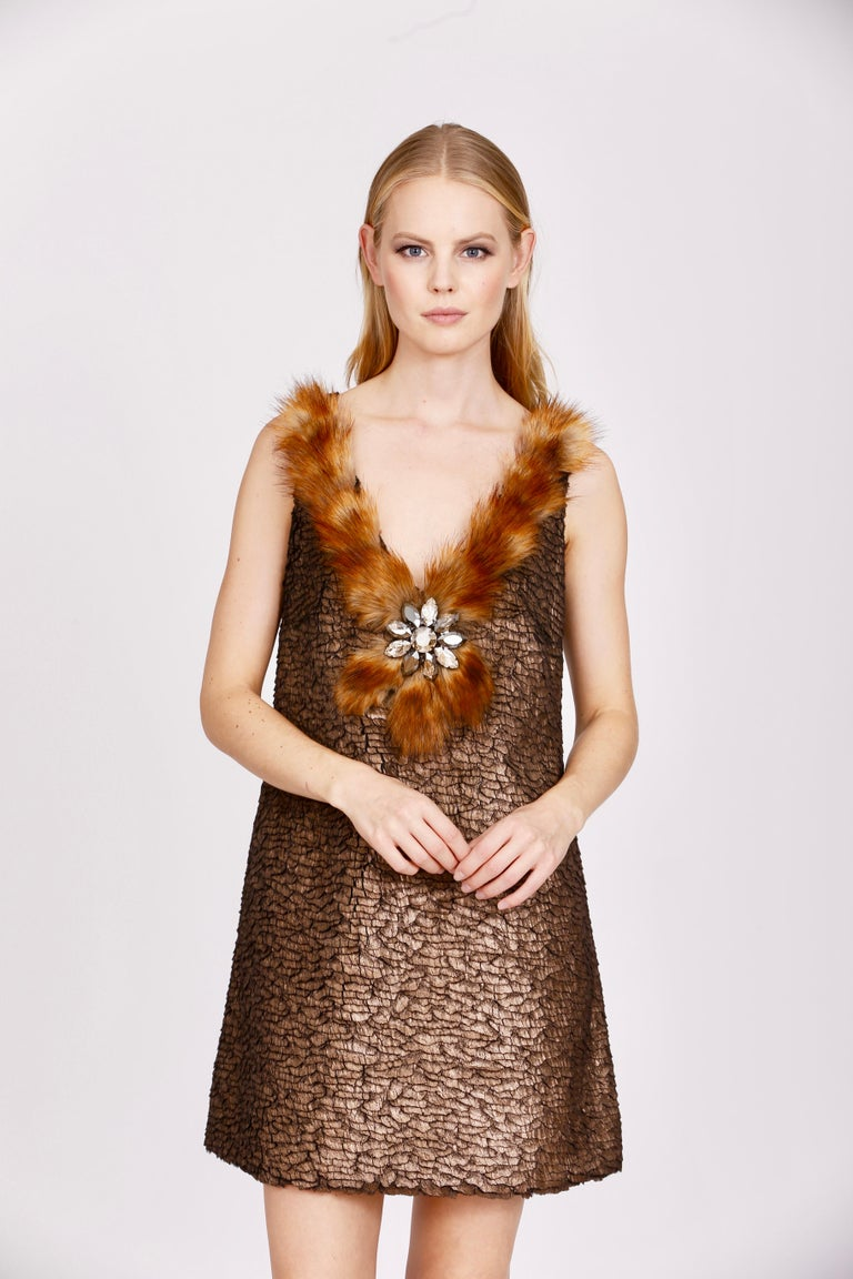 The Vicky Pelush bronze faux fur mini dress with Swarovski flower is a one of a kind exclusive piece. Featuring the highest quality man made pelage, this fur free dress mimics tiny iridescent feathery specks of crushed fake fur and a stunning