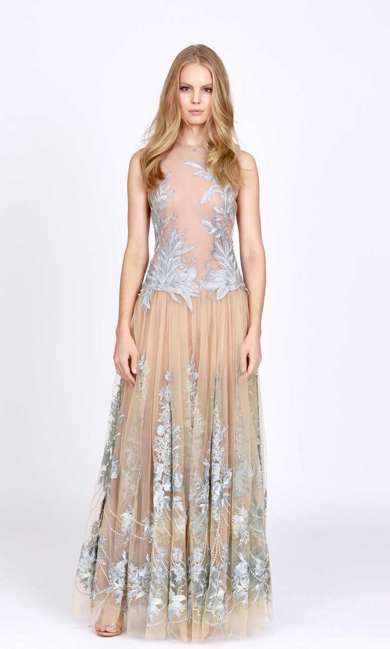 The Elise Pelush nude and powder blue tulle dress gown with floral metallic embroidery is a one of a kind exclusive piece. Adorned with romantic flower bouquet, reminiscent of the 18th Century, delicate hand cut leaves on tulle, this etherial