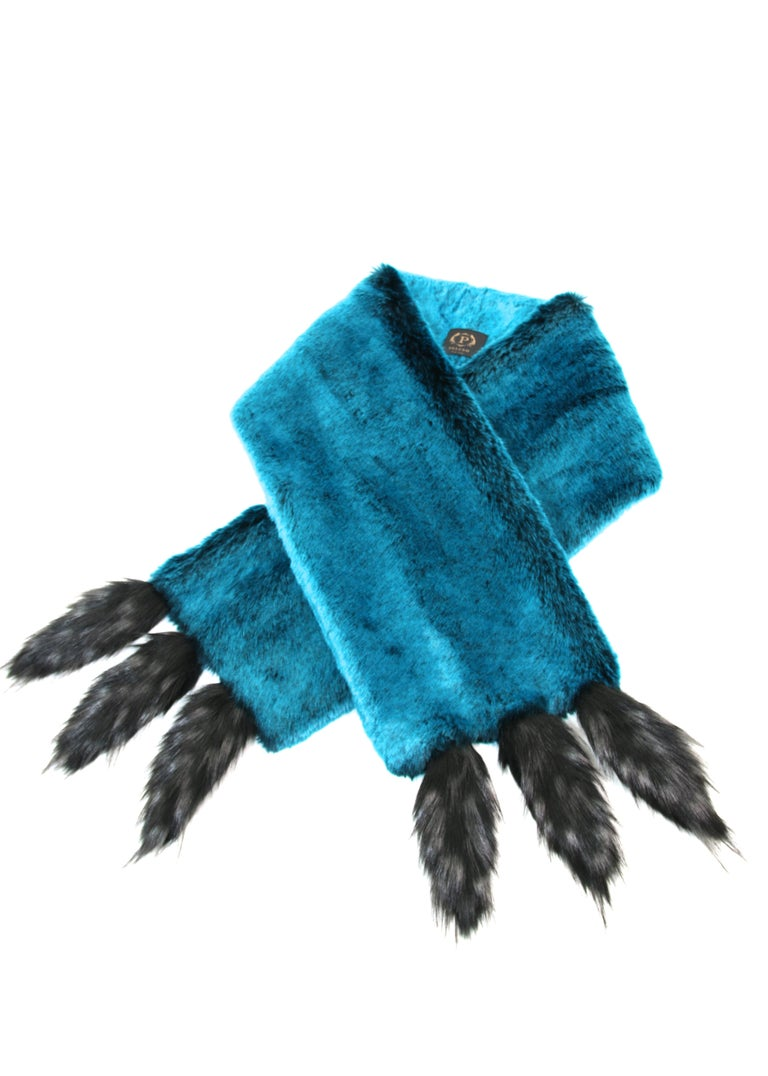 The Anais Pelush teal faux fur chinchilla stole with faux fox fringes is a one of a kind exclusive piece. Featuring the highest quality man made pelage, this eye- catching stole is an extraordinary replica of the chinchilla fur and fox fur.