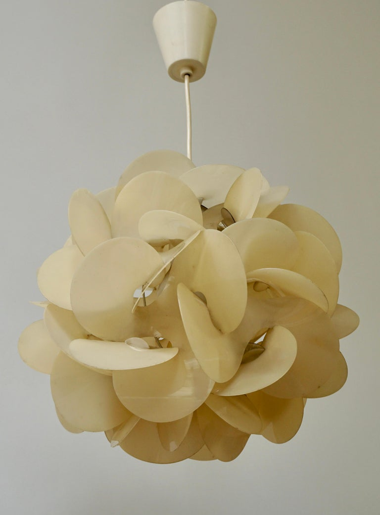 This pendant or ceiling lamp was designed by Raoul Raba. It is made from plastic with a metal wire frame inside.