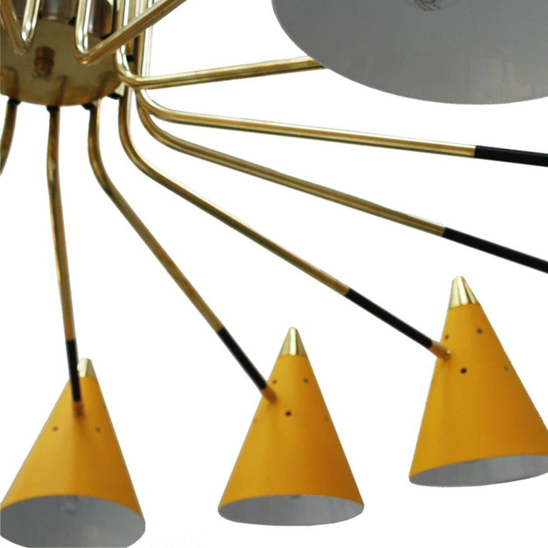 Pendant lamp midcentury style composed of fourteen points of light made of lacquered metal, conical cups and brass details.