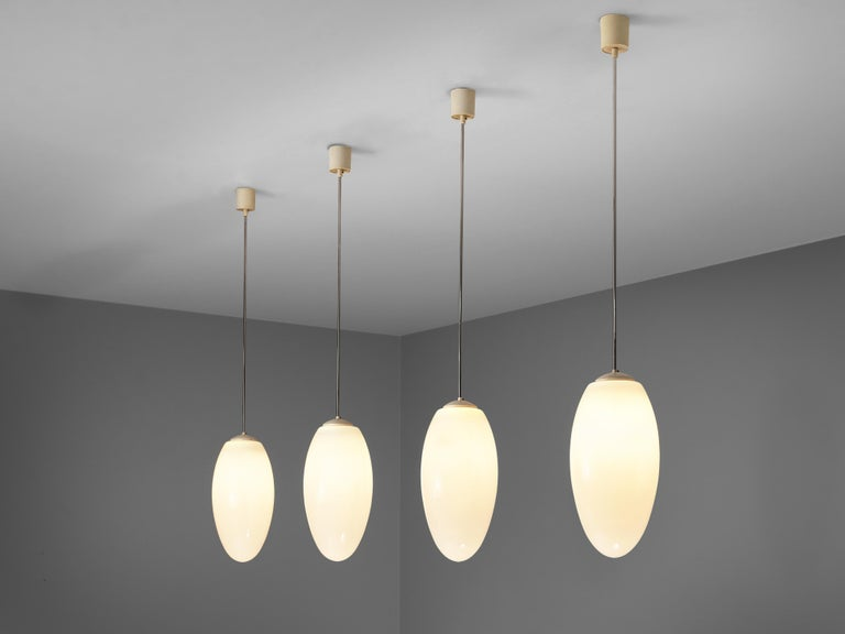 Pendant lamps, metal, opaline glass, plastic, Europe, 1970s  Minimalist pendant lamps with drop-shaped glass shade. The lamps hang on metal stems that end in a cylindric ceiling fixture. The well-balanced, elegant shape of the lamp surrounds the