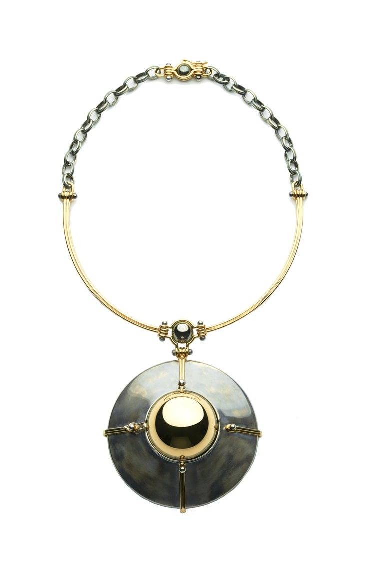 Yellow gold and destressed tarnished silver choker pendant, made of an articulated yellow gold strand and a distressed silver chain. The yellow gold sphere is rotating on a distressed silver structure bound by gold links and opening on a