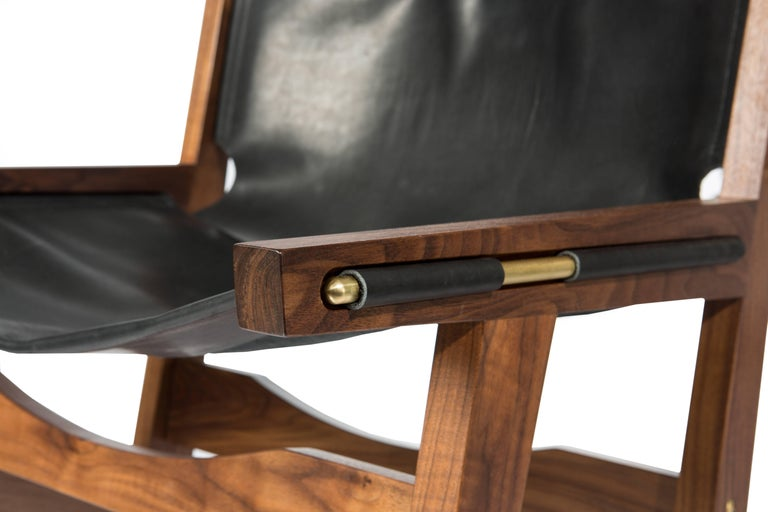 Phloem Studio Peninsula chair is a modern contemporary leather sling lounge chair. The hand crafted solid walnut frame holds the heavy weight bridle leather sling in place with solid shaped exposed brass rods. Appropriate as both a lounge chair or