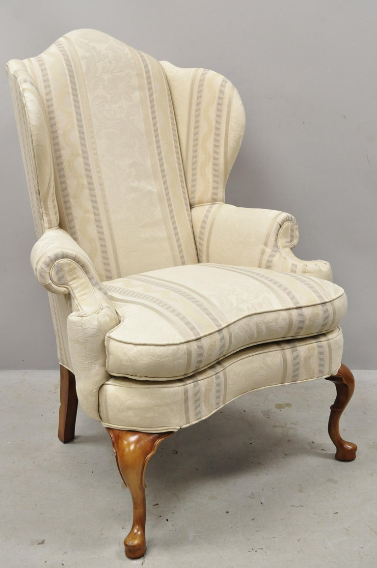 Pennsylvania house Queen Anne rolled arm wingback lounge armchair. Item features rolled arms, tall winged back, notch carved rear legs, bow front, solid wood frame, beautiful wood grain, original labels, shapely Queen Anne legs, quality American