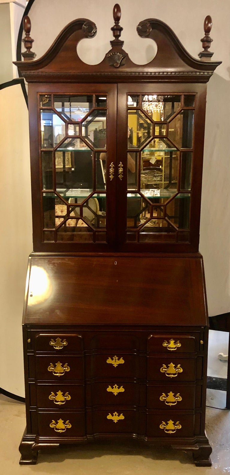 Pennsylvania House secretary desk / bookcase. This fine mahogany block front two-piece Chippendale style secretary bookcase cabinet has a lighted all mirrored with polished edges interior. The drop down slant front having a writing surface with