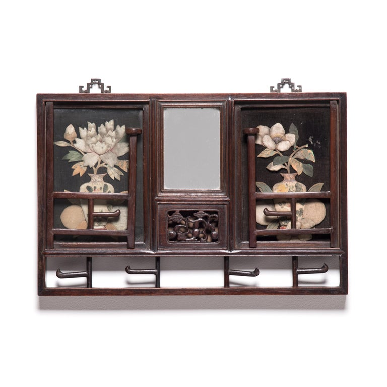 Hung on the wall of a Qing-dynasty home in northern China, this remarkably crafted hat rack provided the kind of elevated display that status-enhancing hats demanded. Flanking the central mirror and carved rosewood panel, floral still lifes are