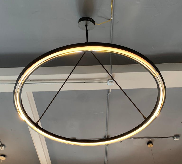 Classic craftsmanship meets modern innovation in this lighting collection from industrial blacksmith Jon Sarriugarte. Forged from iron, the fixture's clean contours conceal eco-friendly LED light strips, providing a halo of ambient