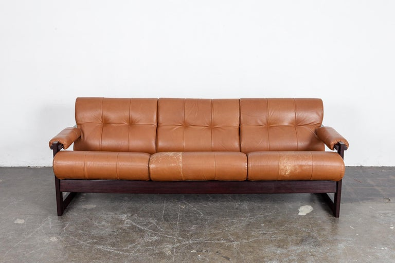 Percival Lafer designed 3-seat tufted sofa in original burnt orange leather with jatoba wood frame, model MP-167, produced by Lafer MP, Brazil, 1960s. Leather shows some patina and wear, consistent with age, especially on 2 of the seat cushions as