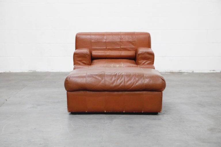 An impressive cognac colored leather lounge chair and ottoman by Brazilian designer Percival Lafer, with original labels, circa 1960 in original leather with moderate attractive patina and features a unique ability for the arms to transform up or