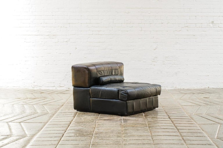 A modular black leather sofa with innovative articulated arms ( can be up or down into the unit) the back lifts off to reveal some storage. Amazing as a pairs of chairs, or two smaller sofas.  These four pieces can be arranged as two pairs single