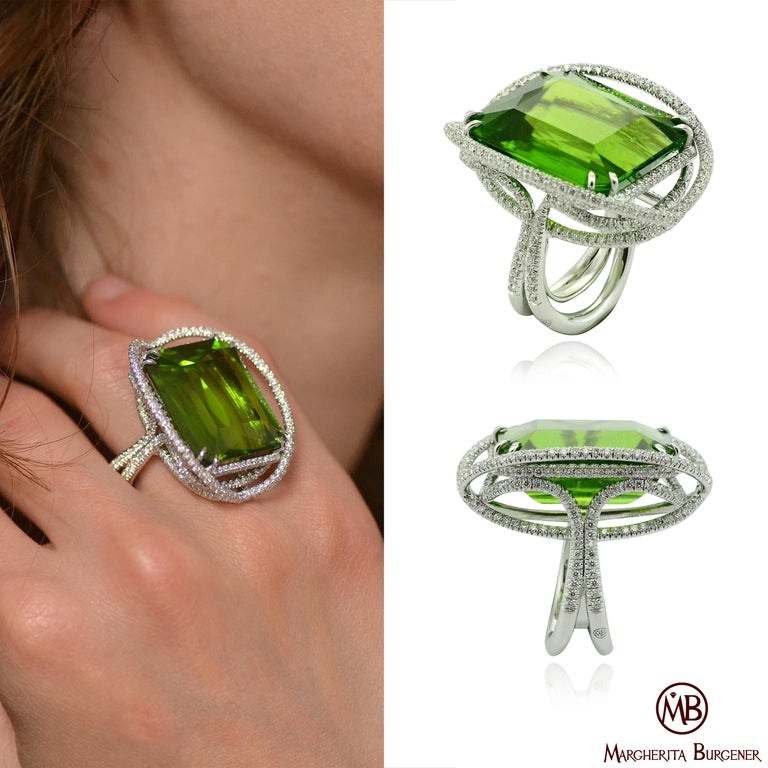 An impressive Peridot of Burma origin, wighing 53.50 carat is centering the Ellissi ring. a handcarved wire, all aroung the stone, is designing an enchanting motif and it is fully pavé set with diamonds. The deep green color of the peridot is