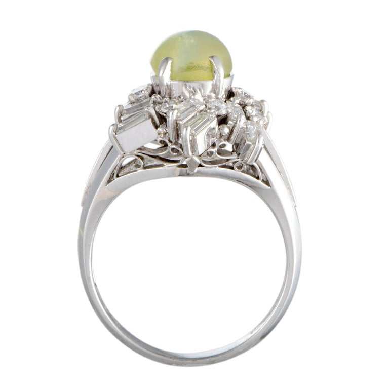 The intricate design and the resplendent diamond décor create a compelling pedestal for the intriguing cat's eye stone in this fabulous ring. The ring is made of platinum and boasts a total of 0.93 carats of diamonds, while the cat's eye stone