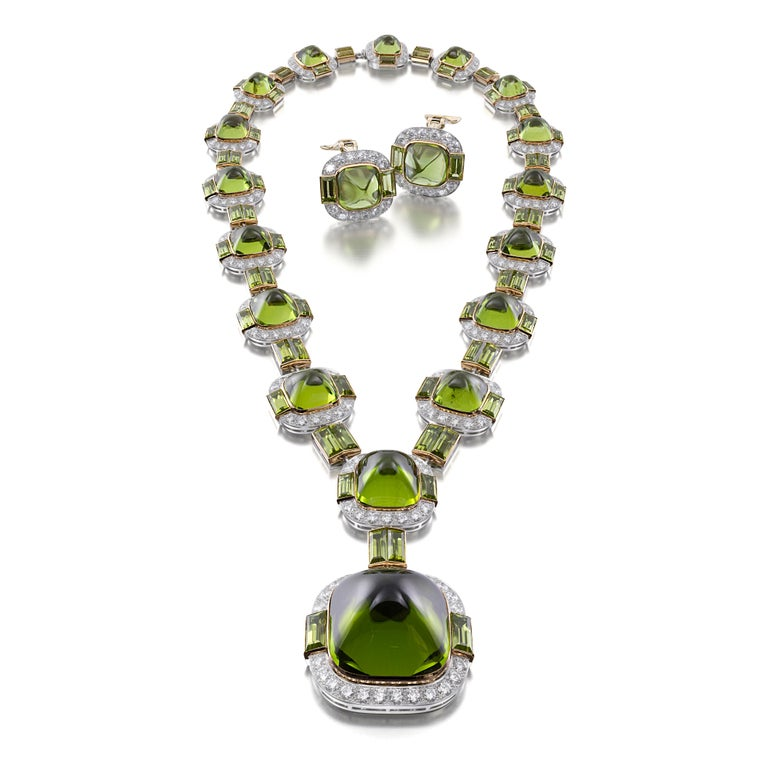 A necklace designed with a series of graduating stations, each centered with a sugar-loaf peridot and highlighted with baguette-cut peridots and round brilliant-cut diamonds, joined by links of baguette-cut peridots; ear clips en suite; mounted in