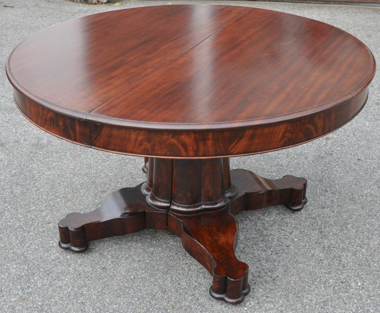 Period New York Classical Empire dining table with four leaves.  Signed by Charles hope, New York  --Crotch Mahogany and solid top boards. --Composite Gothic column base with splits in extension. --Four clover ended feet --Leaves are