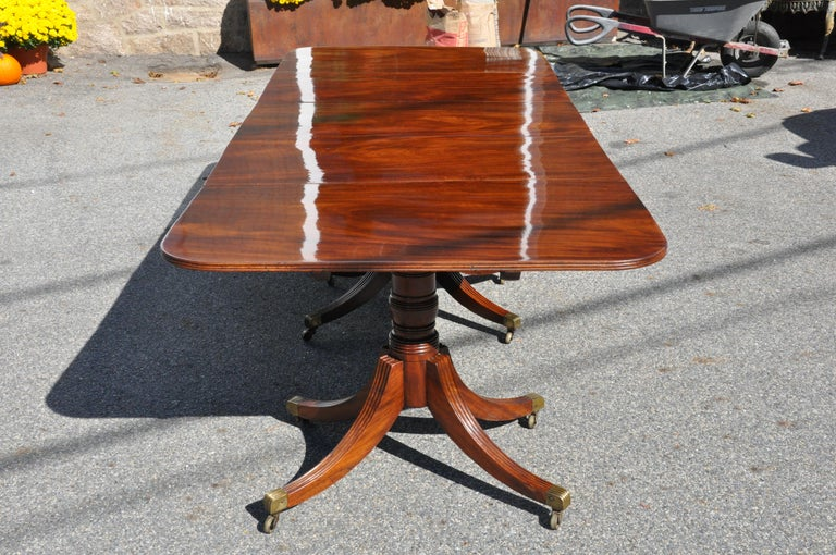 Period American or English three pedestal dining table with two additional leaves.